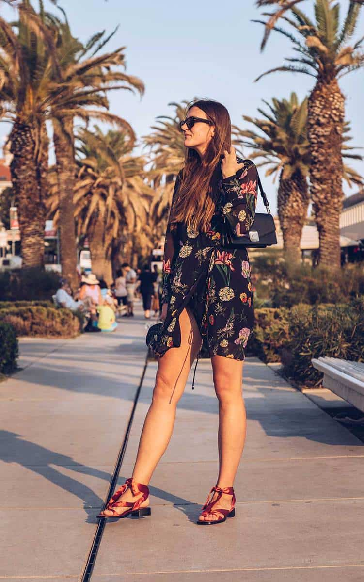 Attractive woman in a floral mini dress, wearing sunglasses and holding a small black bag
