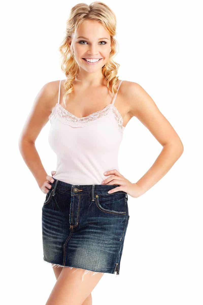Attractive young blonde woman in blue denim skirt and white cami top