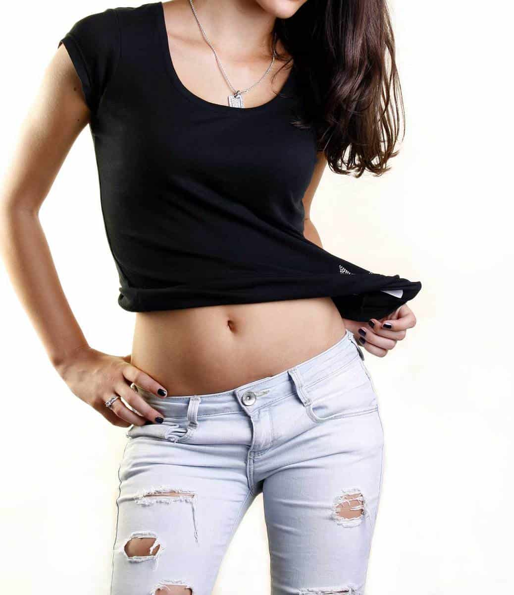 Beautiful female model in jeans and black shirt isolated on white background