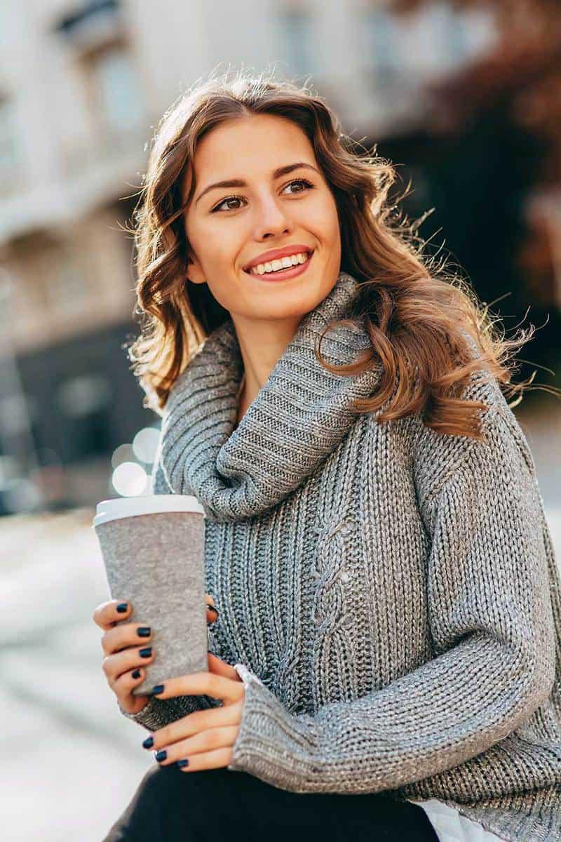 Beautiful woman wearing grey turtle neck drinking coffee