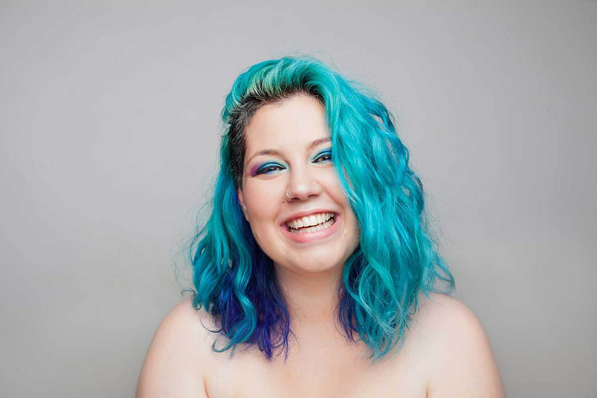 Beautiful woman with colorful blue hair smiling