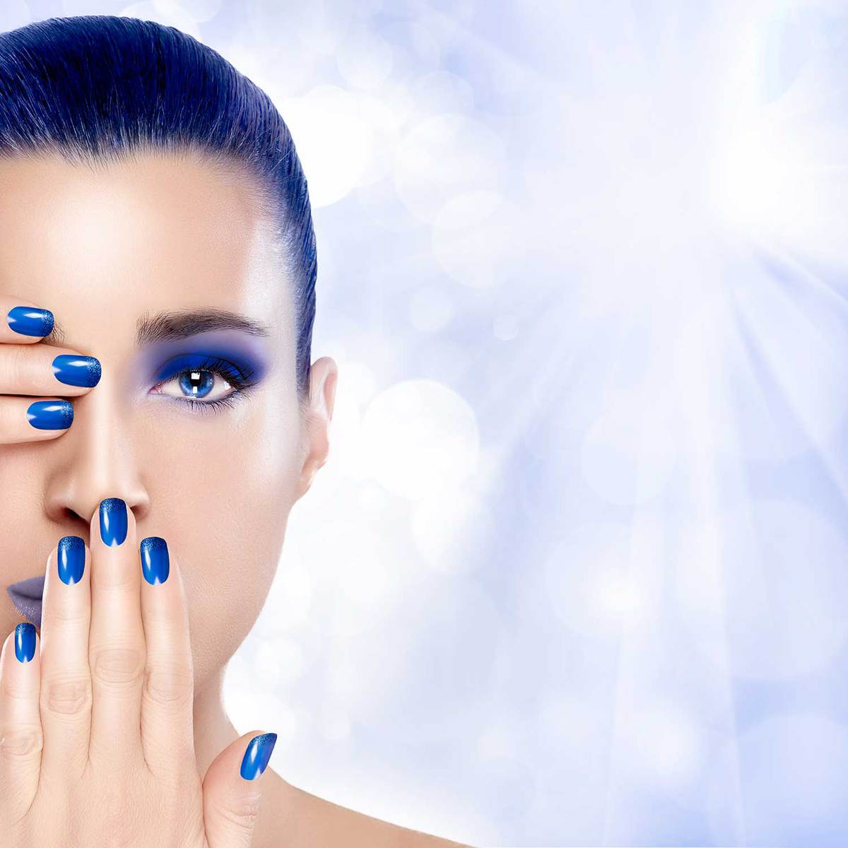 Beautiful young woman with blue hair, nails and makeup with hands on her face covering one eye and mouth
