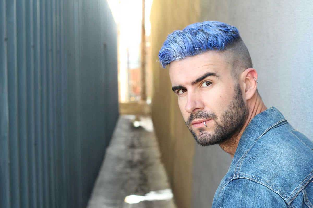 Handsome stylish young man with blue undercut hairstyle