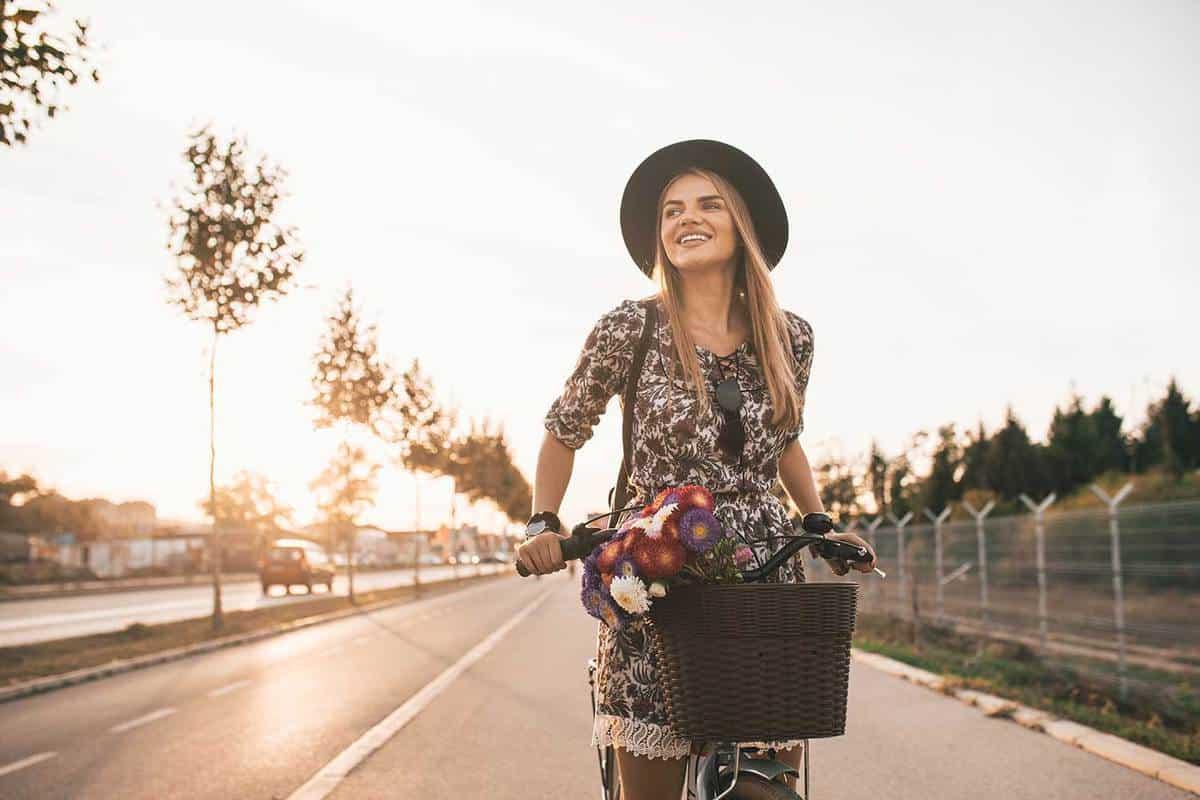 Happy woman in a floral outfit with hat and bicycle