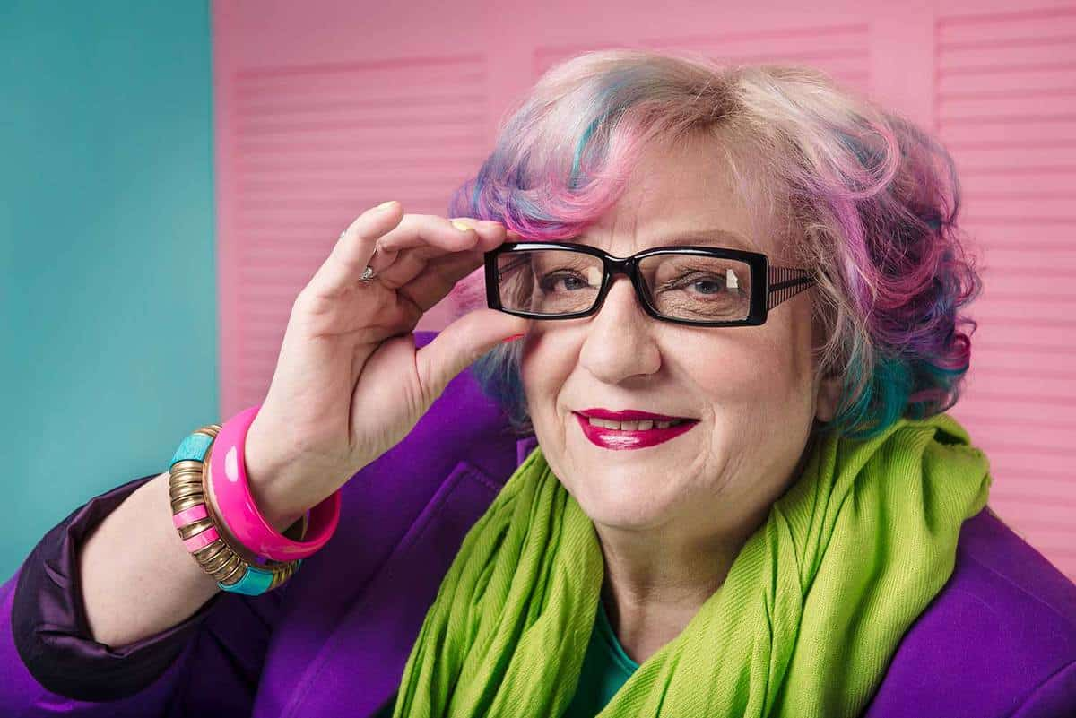 Stylish senior woman with colorful hair wearing prescription glasses with black frame