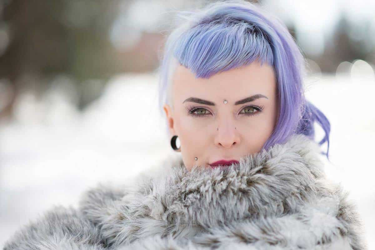 Winter shot of young woman with lavender hair wrapped with fur coat