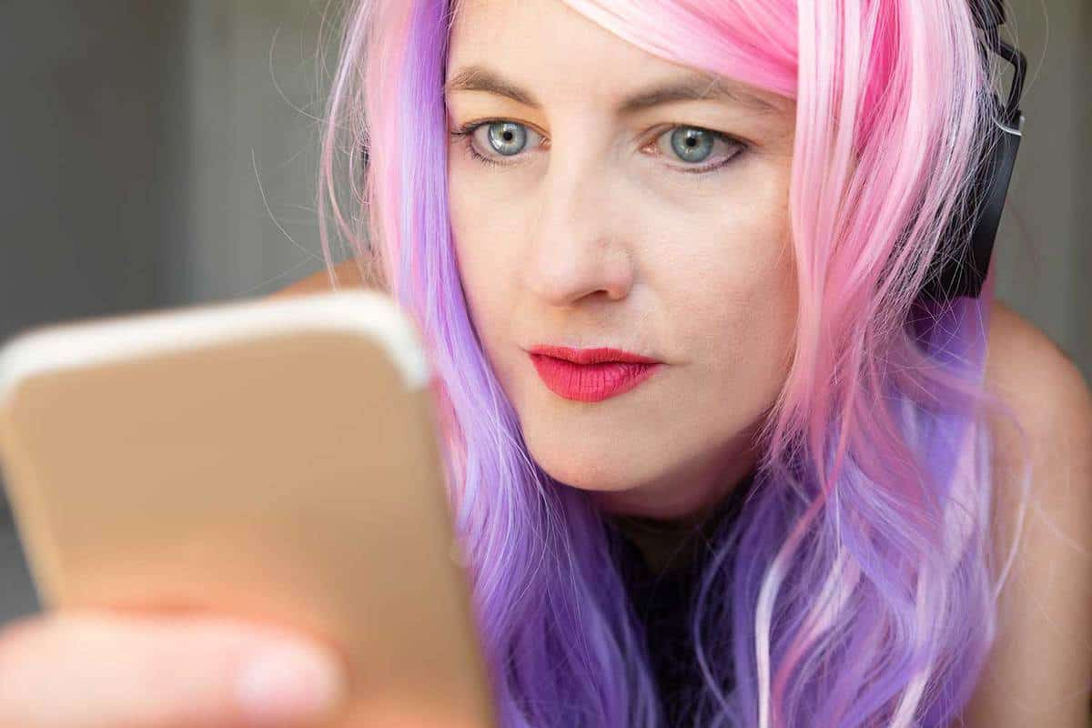 Woman with pink and purple hair listening to music