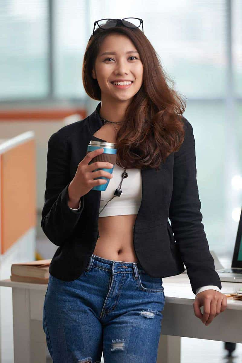 Young asian woman in crop top and jacket drinking take-out coffee