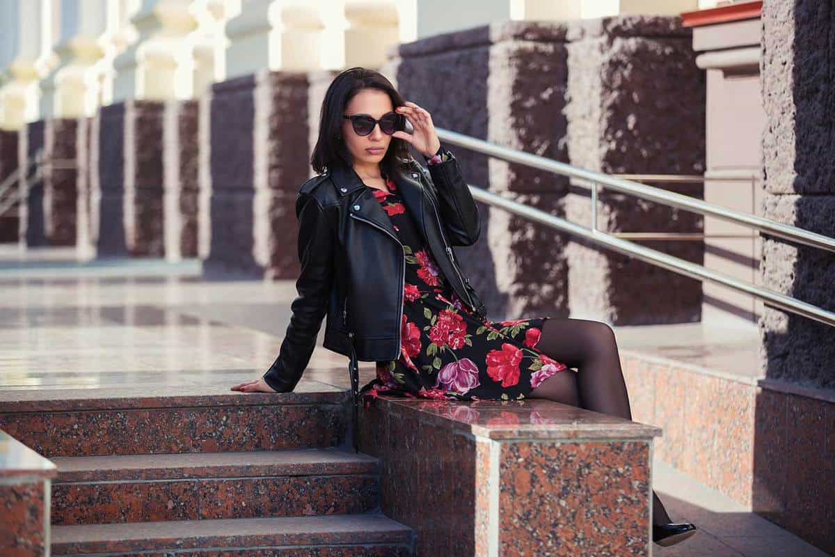 Young fashion woman in leather jacket and floral dress