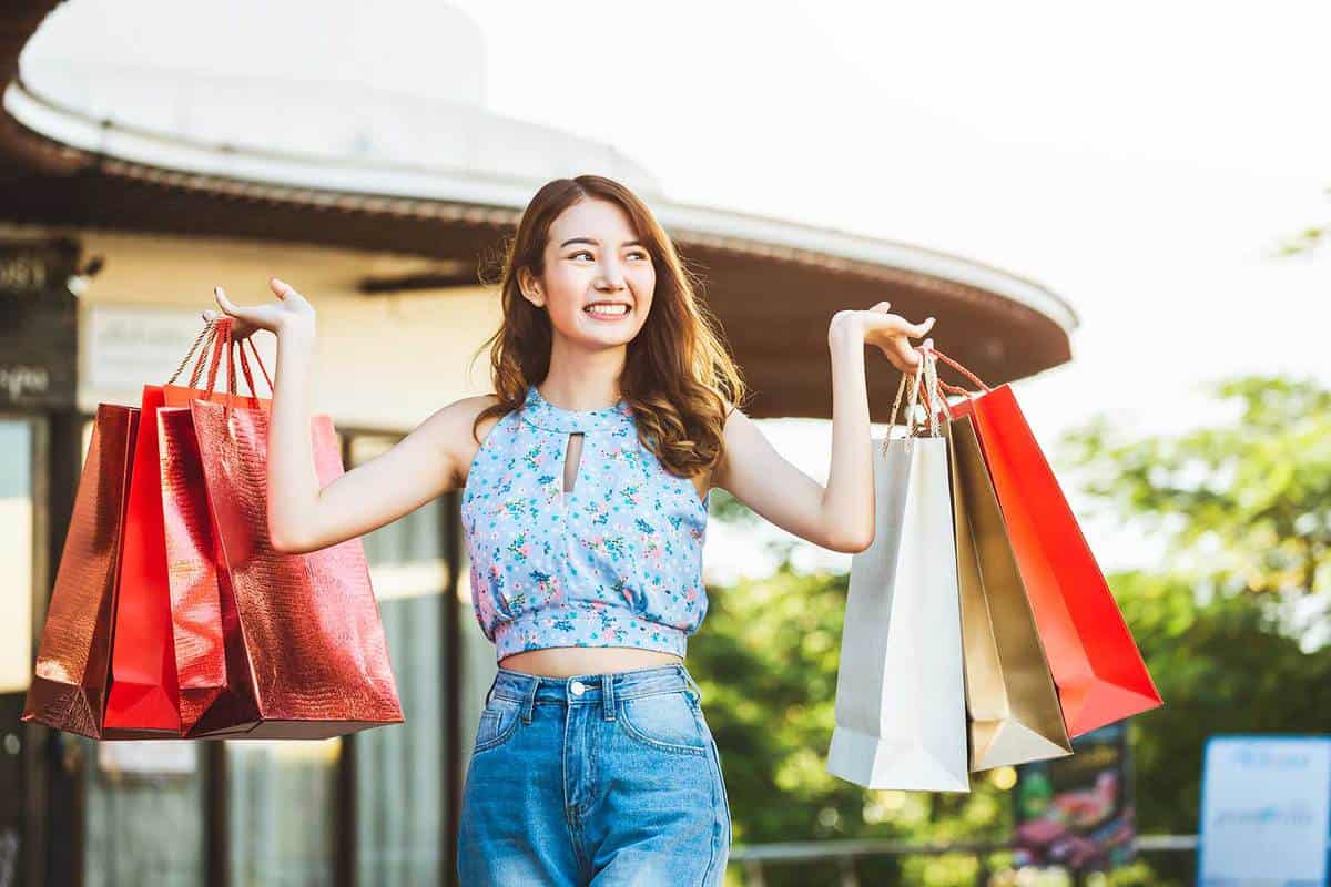 Young happy asian woman with paper bag wearing crop top and jeans
