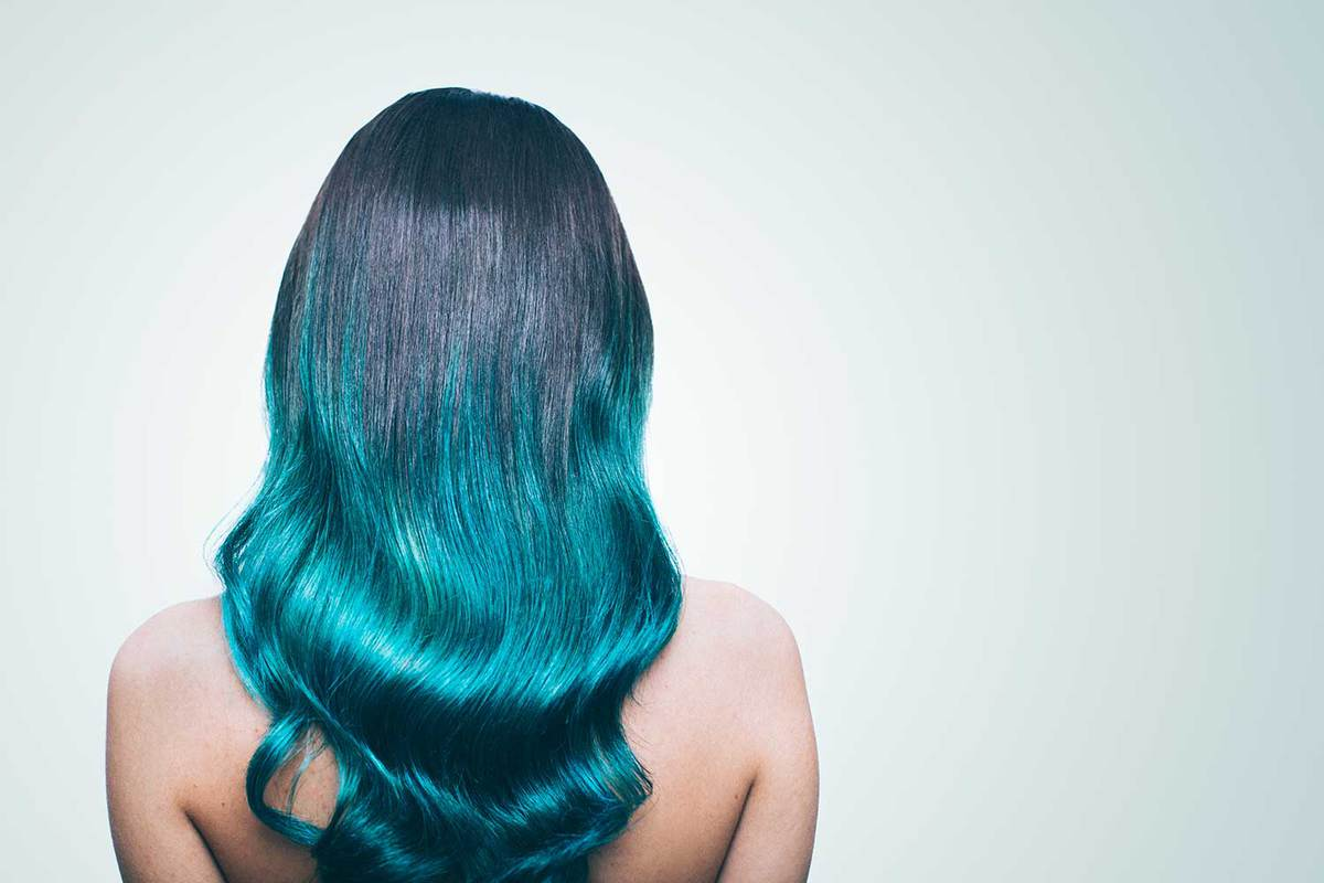 Young hipster girl with a turquoise dyed hair in an ombre coloring technique