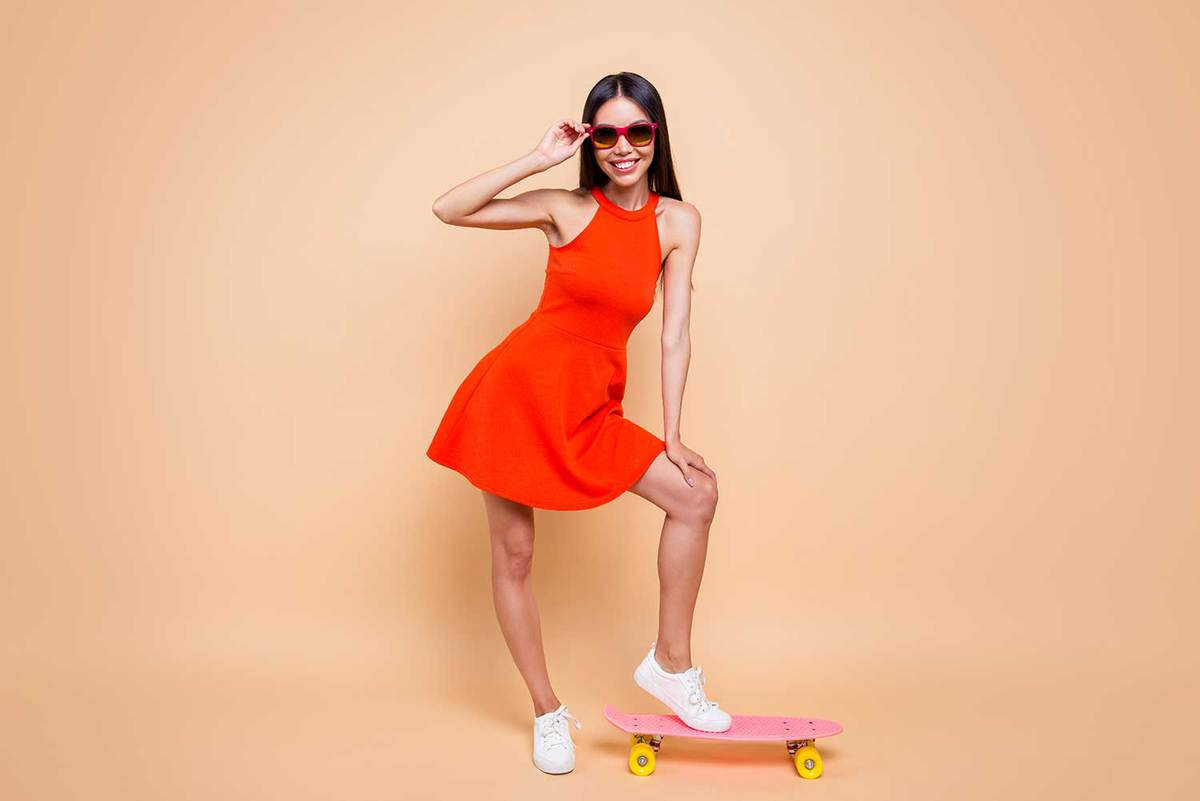 Attractive lady wearing red dress posing standing holding leg on pink longboard isolated on pastel beige