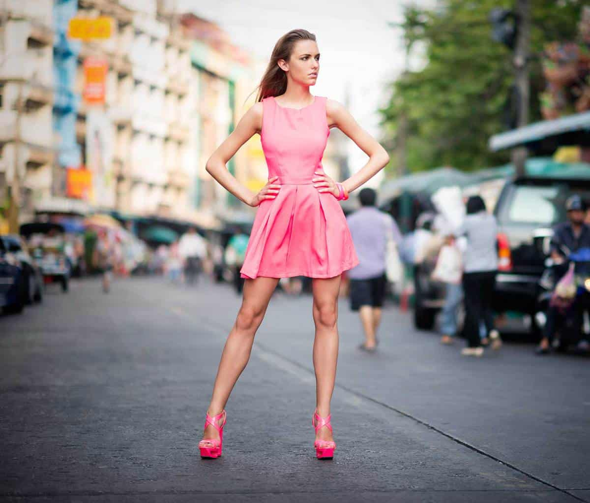 Beautiful model in pink dress and sandals posing in a side street