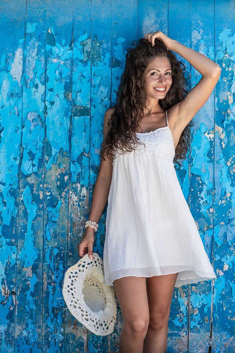 Woman in a summer white dress standing in front of old blue wooden wall