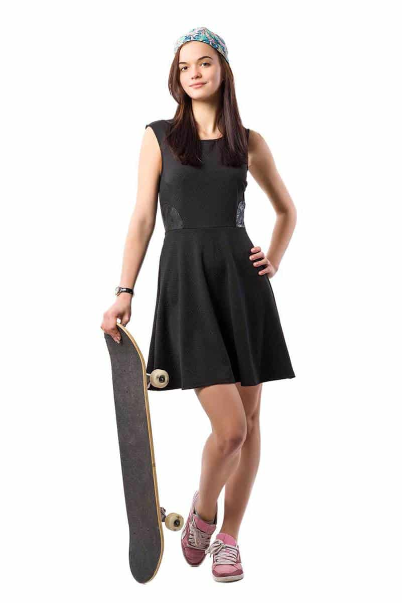 Young girl in black dress standing with a skateboard