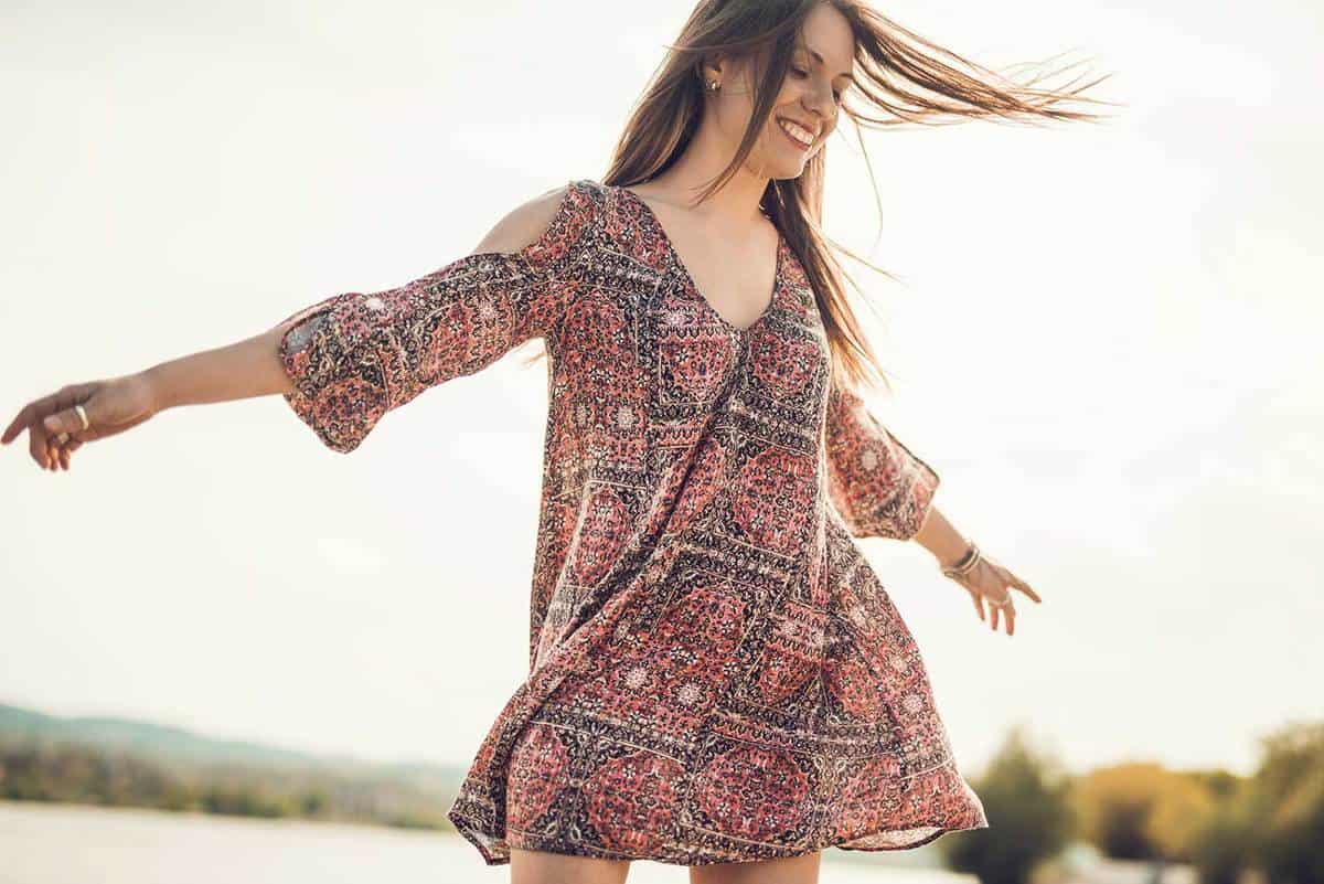 Young happy woman in dress having fun outdoors while spinning with her arms outstretched