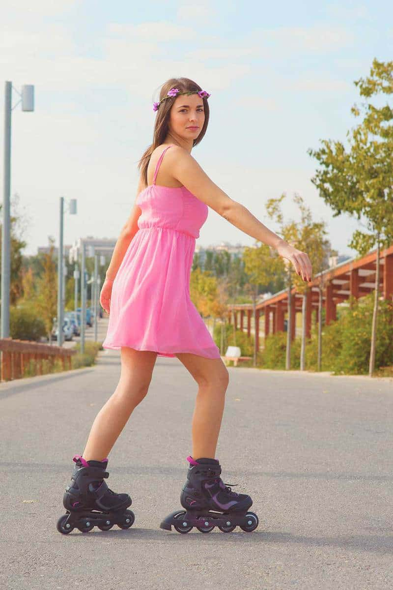 Young teenage girl in pink dress uses her skates in the park