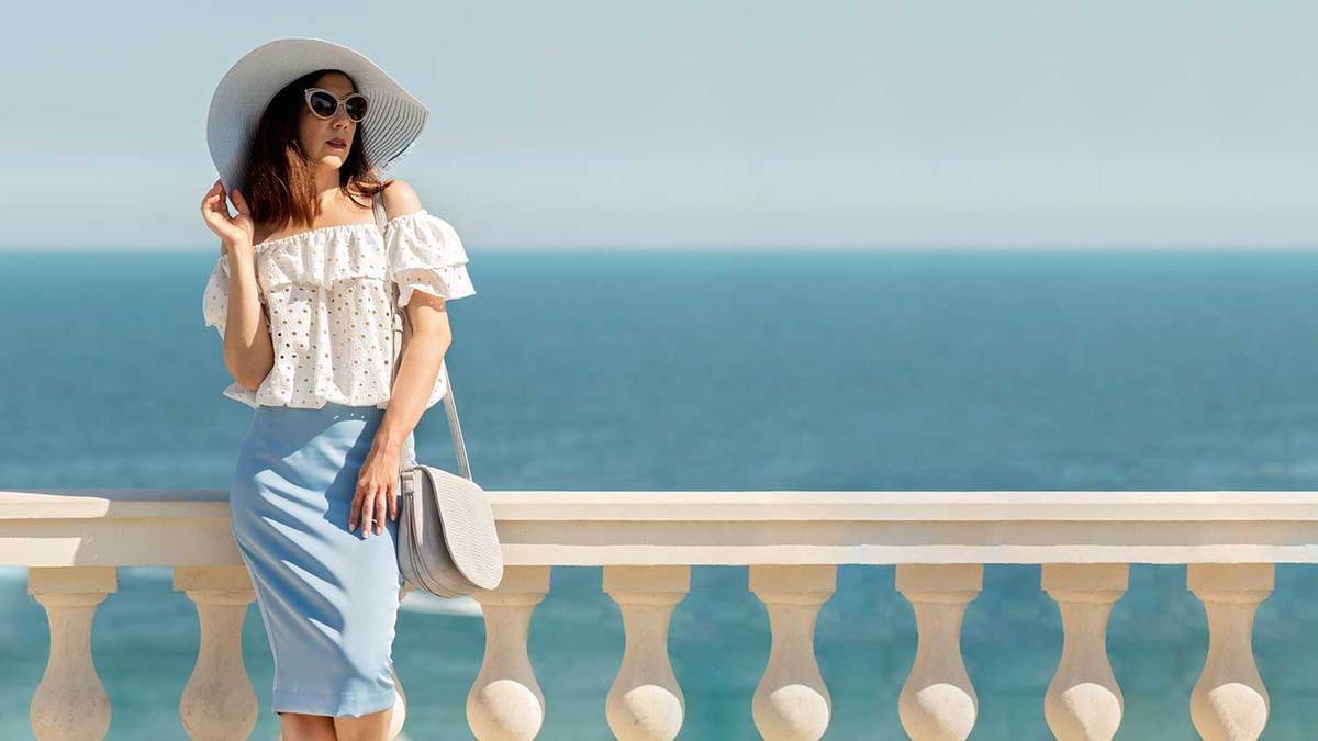 Young woman in off shoulder white blouse, blue pencil skirt and hat