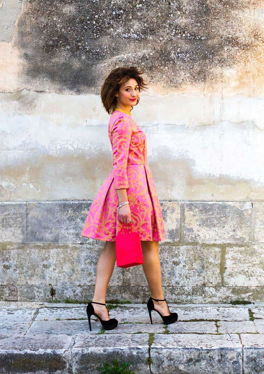 A chic young European beauty in a pink dress and black stilettos walking with a pink shopping bag