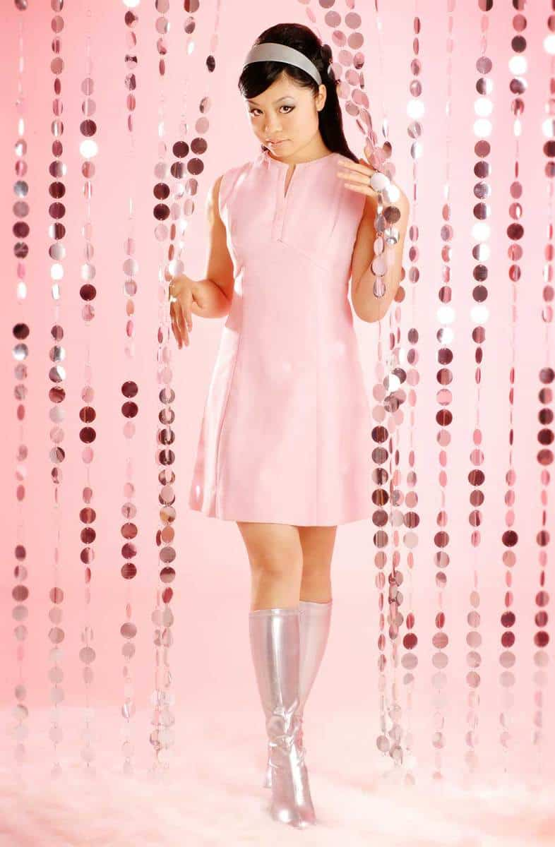 Asian woman dressed in retro style pink dress and silver boots