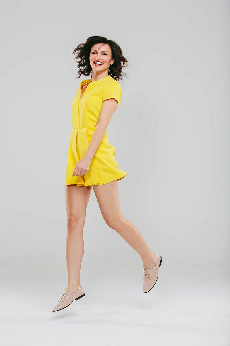 Attractive woman in a yellow dress posing against gray background