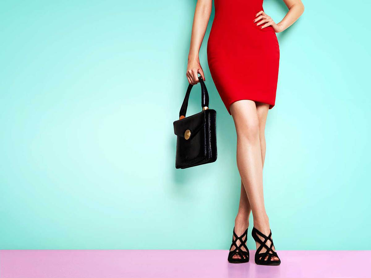 Beautiful legs woman wearing red dress, black heels and black purse standing against teal wall