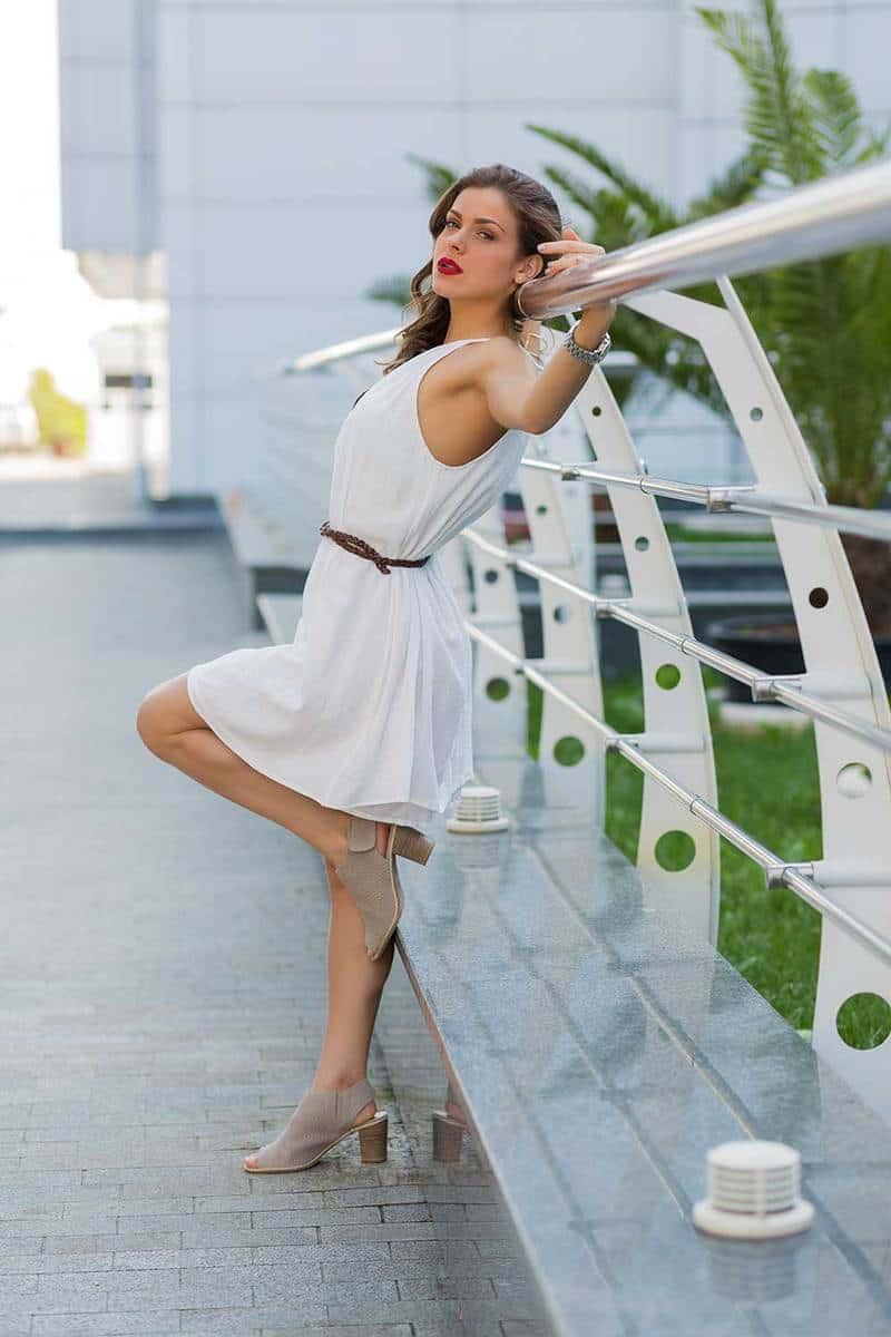 Beautiful stylish woman in white dress posing on the street