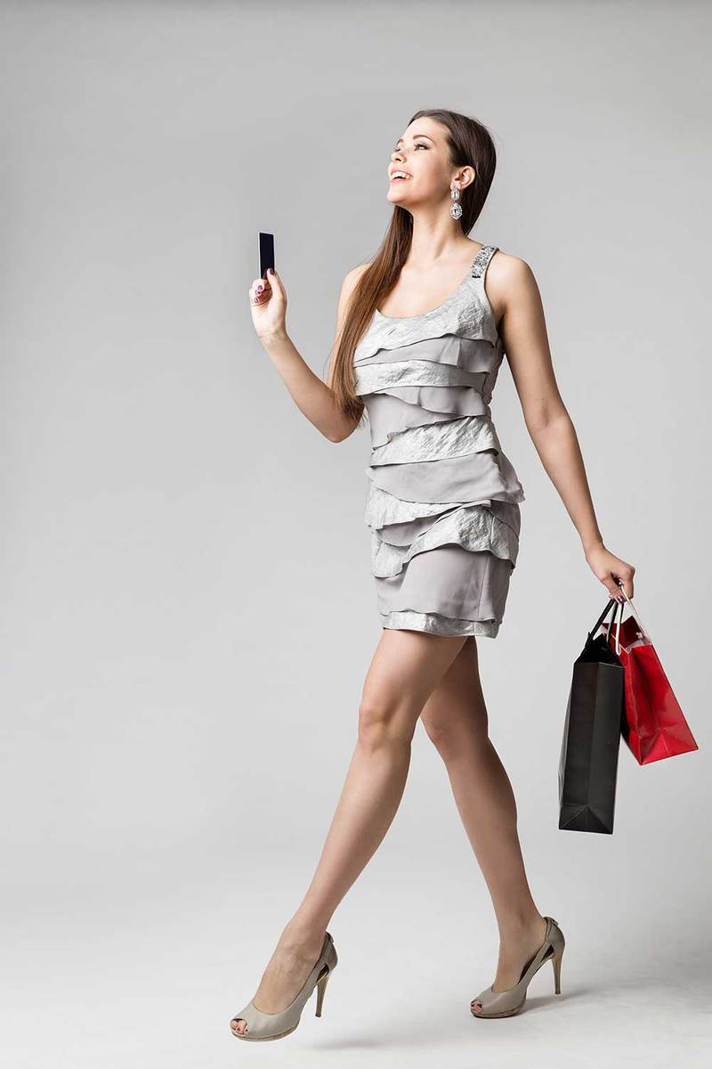 Beautiful woman in grey dress holding a credit card and shopping bags