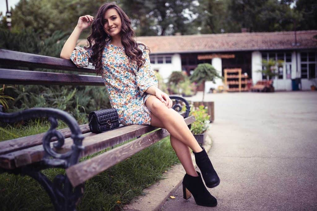Beautiful woman sitting on the park wearing half sleeve floral dress with black boots and purse