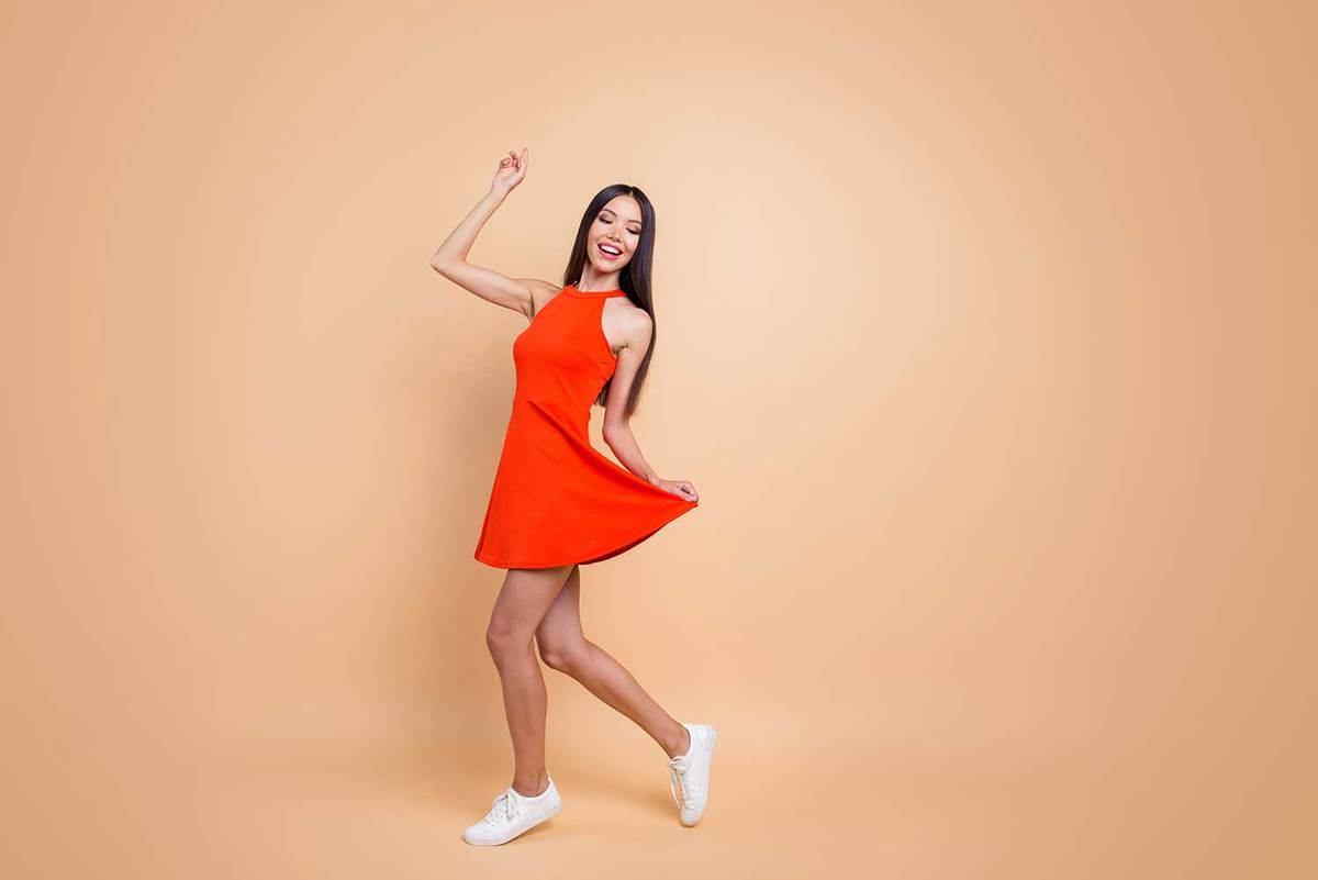 Cheerful gorgeous teen lady in red dress and white sneakers