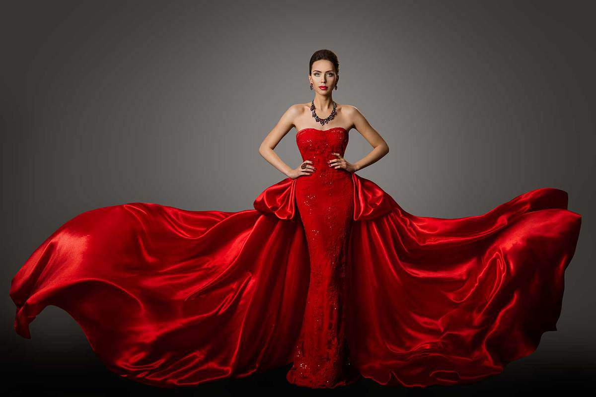 Fashion model in in long fluttering waving red gown and statement necklace
