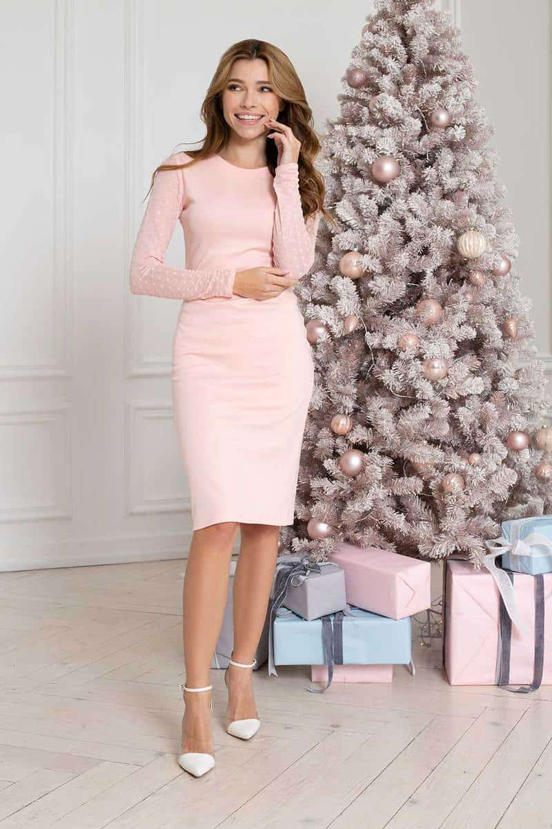 Gorgeous women in a long beautiful pink evening dress and white heels standing near Christmas tree