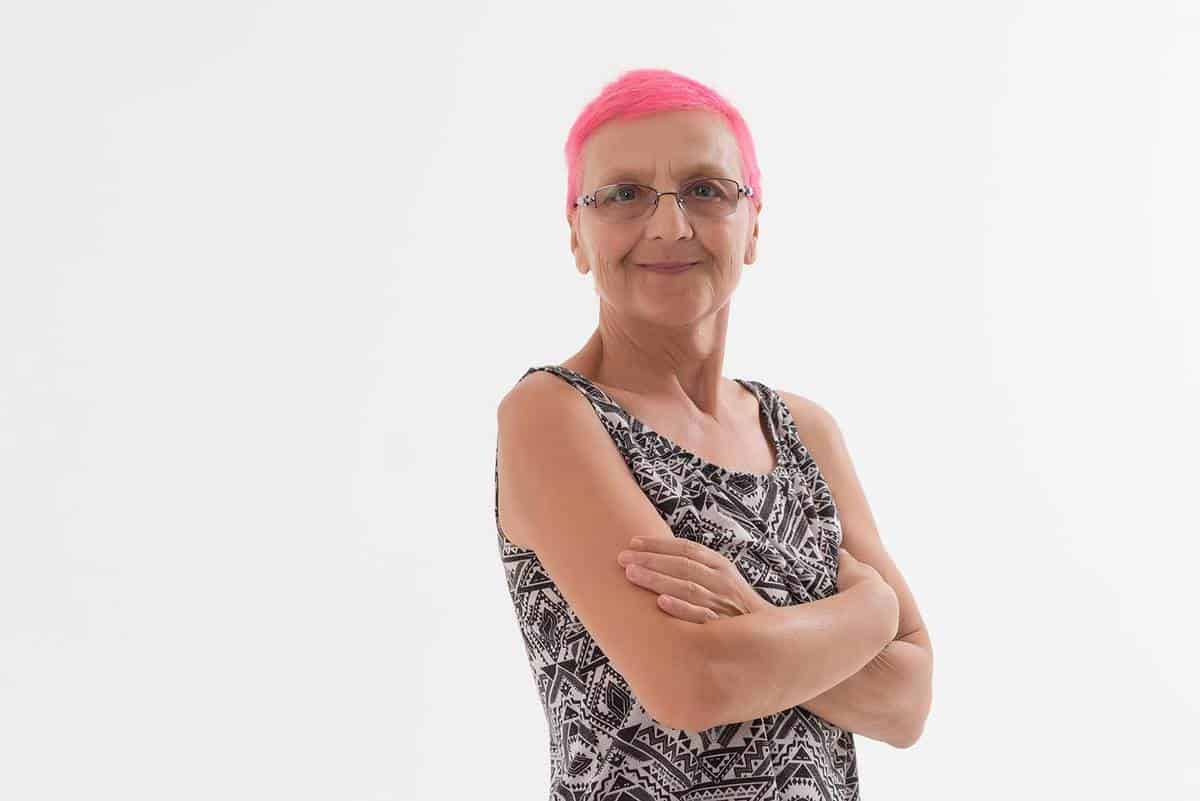 Happy senior woman with pink hair smiling on white background
