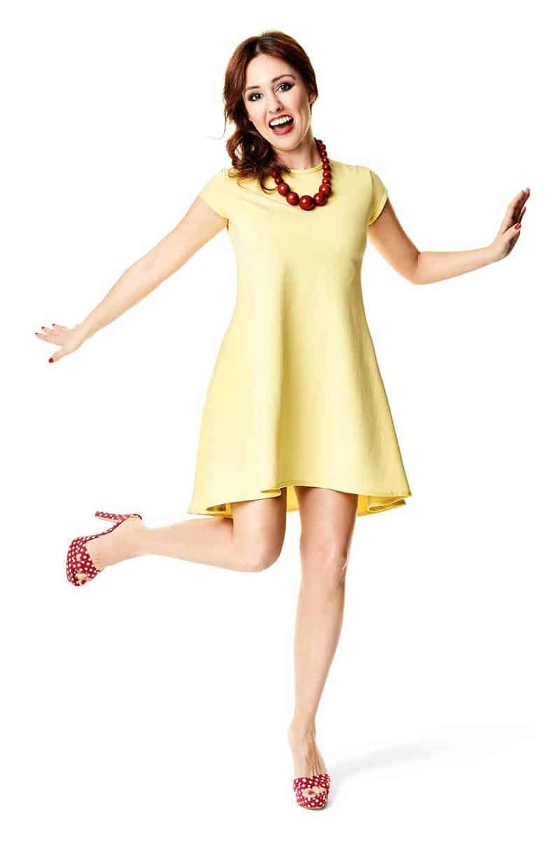 Happy woman dancing in yellow dress and red polka dot shoes