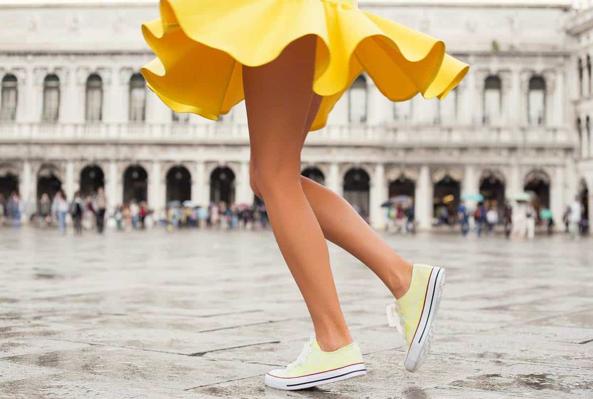 Happy woman in bright yellow skirt and yellow sneakers