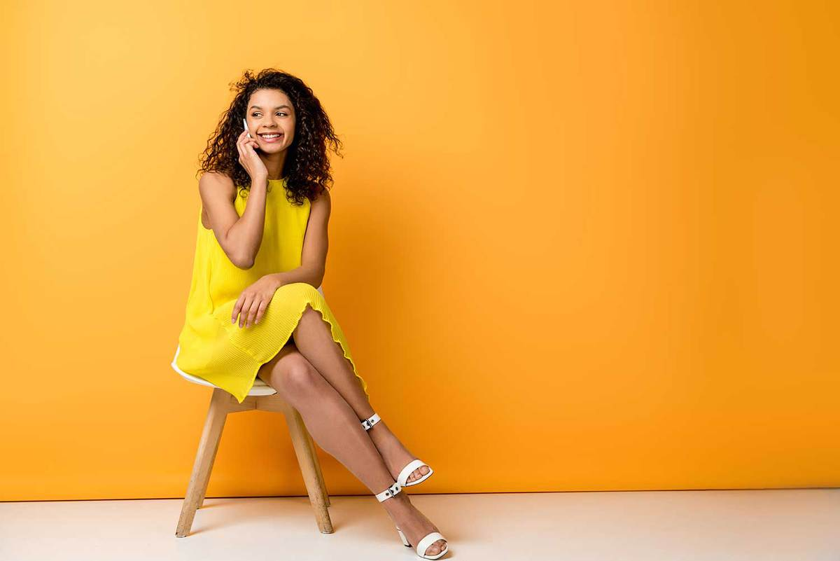 Happy woman with curly hair wearing yellow dress and white heels sitting on a chair and having a call