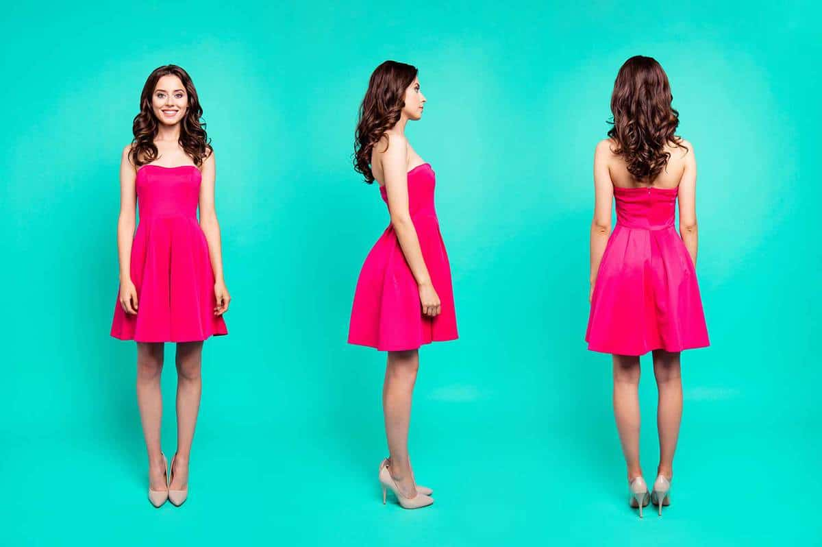 Portrait of an attractive, curly brunette lady in pink dress and high heels