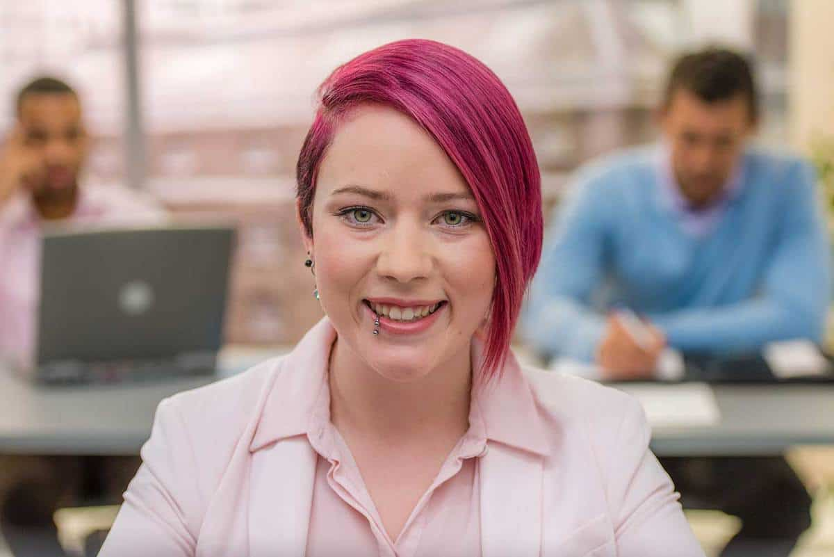 Portrait of woman with pink hair smiling in an office