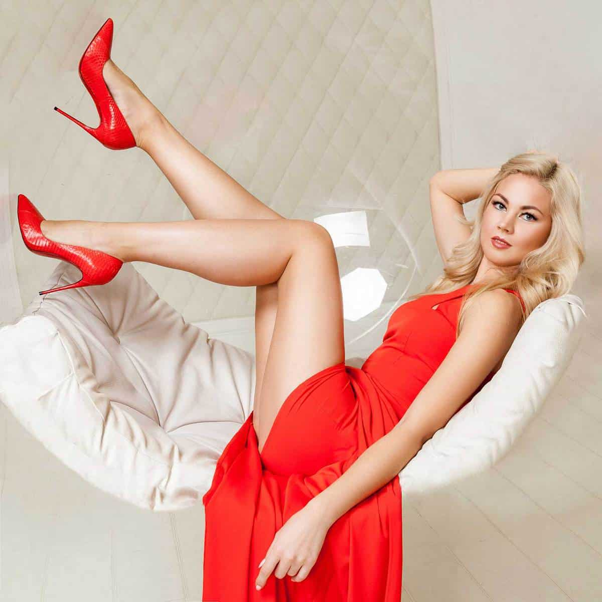 Sensual fashionable blonde young woman in bright evening red dress with makeup and matching red shoes, curly hairstyle lying and posing in hanged bubble chair