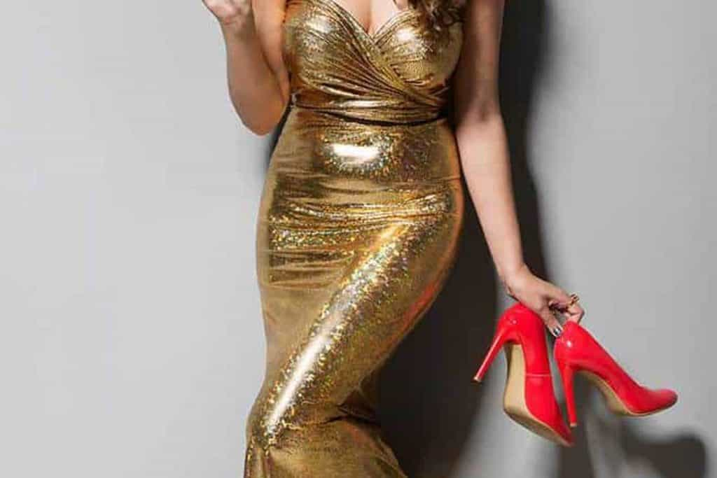 Sexy woman wearing gold dress and holding her red shoes