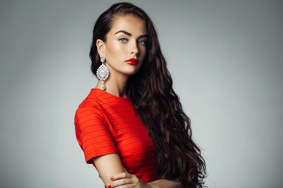 Studio shot of young beautiful woman wearing red dress and dangling earrings
