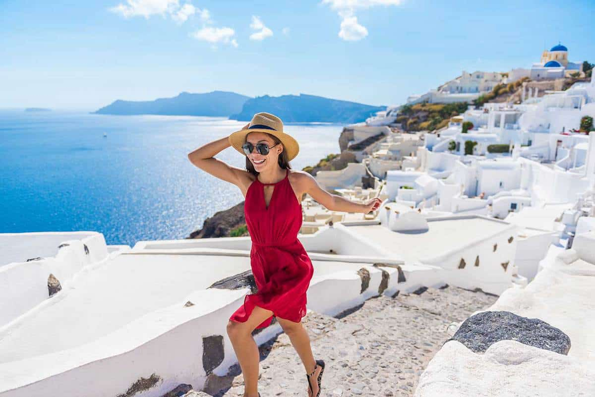 Tourist woman wearing red dress and hat, running stairs in Santorini, Greek Islands, Greece