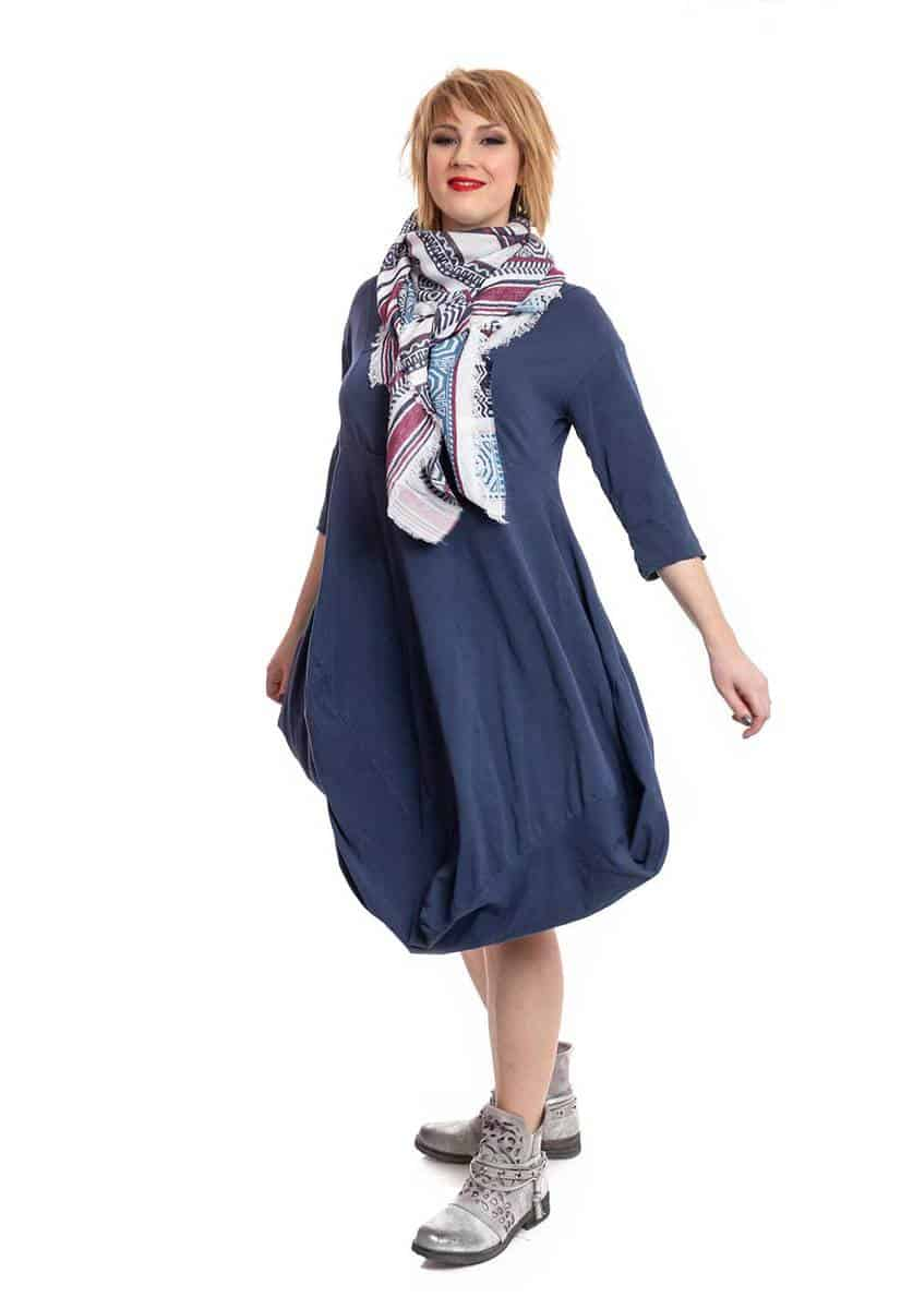 Woman wearing blue dress and scarf on white background
