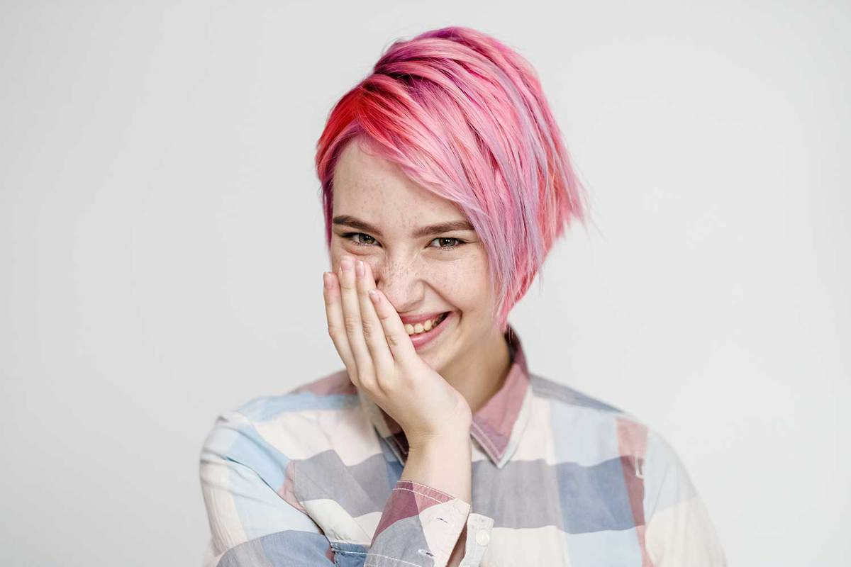 Young beautiful girl with short pink pixie bob haircut in white background