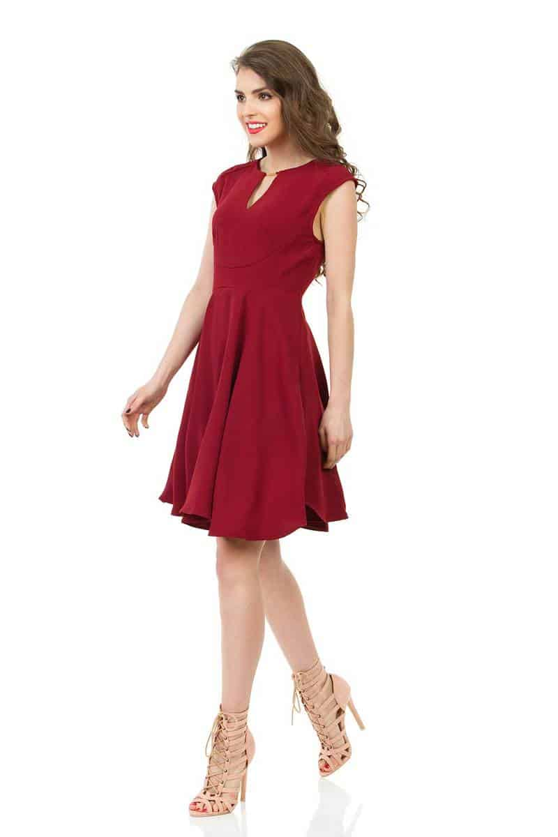 Young beautiful woman in red dress and high heels walking, looking away and smiling