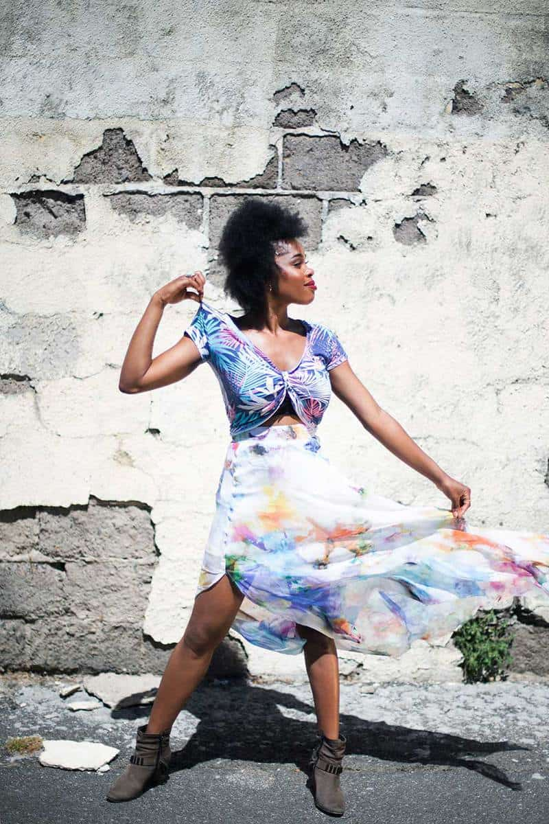 Young model wearing boots and colorful dress poses with one arm outstretched and the other to her shoulder against a dilapidated wall