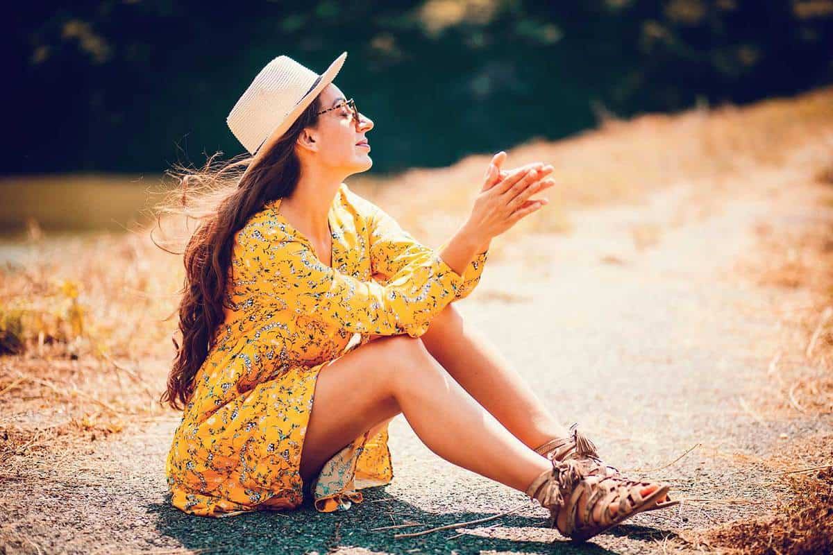 Young woman sitting on the rural road wearing yellow dress and brown sandals in bohemian style fashion