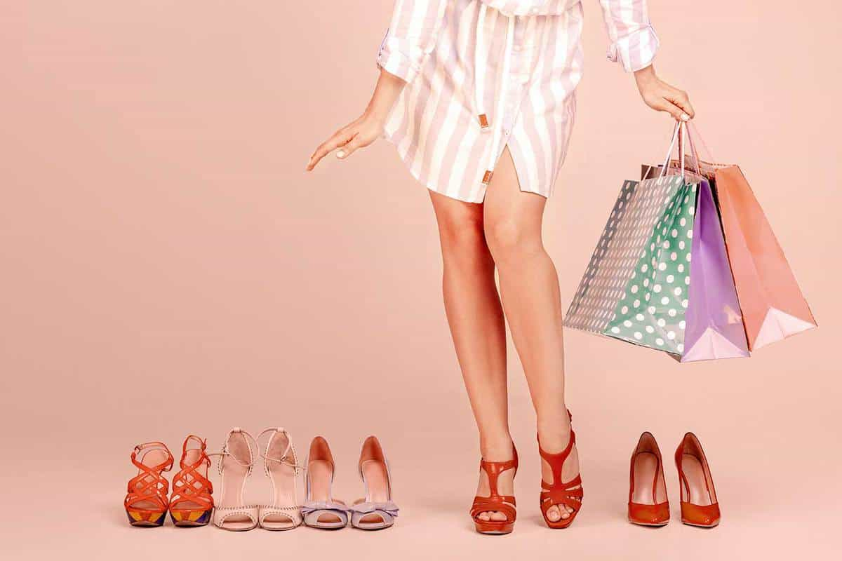 Young woman with shopping bags stands between new pairs of shoes