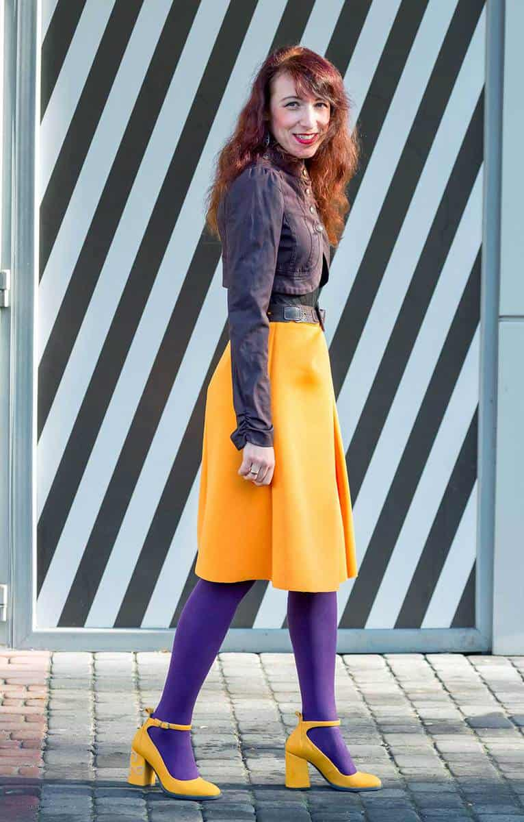 Beautiful stylish brunette young woman wearing bright yellow skirt, purple tights and high heels