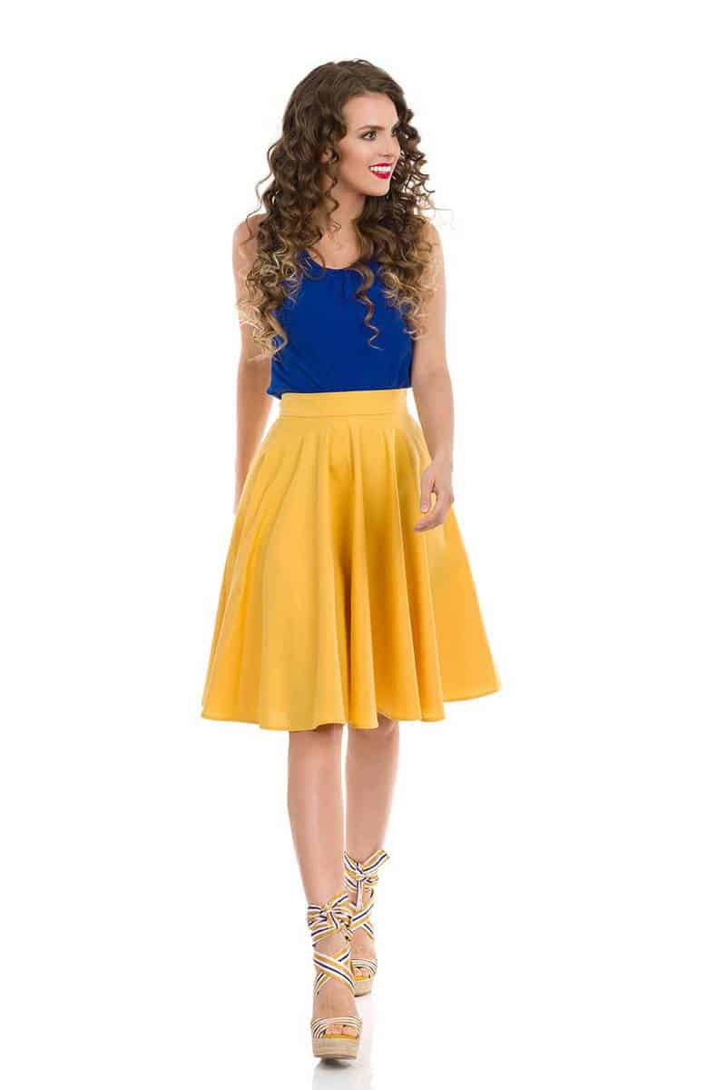 Beautiful young woman in yellow skirt, blue top and wedges
